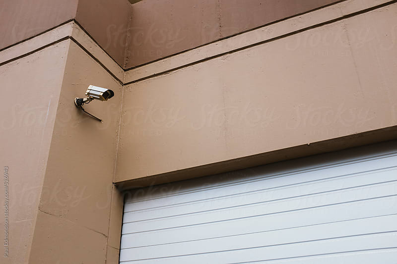 Surveillance camera in front of garage door by Paul Edmondson for Stocksy United