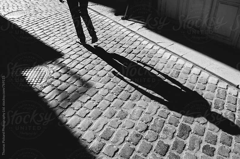 Man's shadow on cobblestones, Baku, Azerbaijan. by Thomas Pickard for Stocksy United