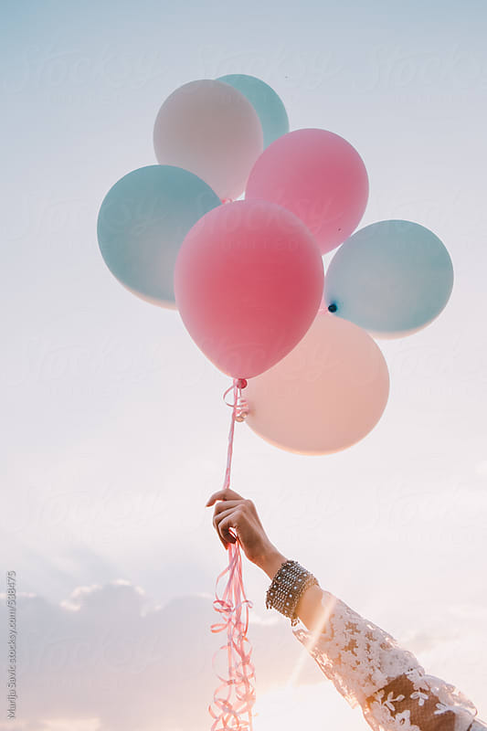 Woman Holding Balloons by Marija Savic for Stocksy United