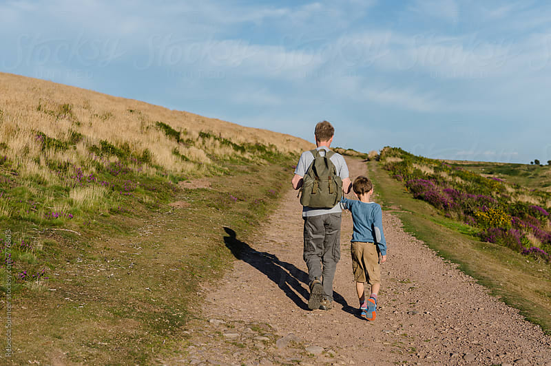 Arm in arm Dad and child walk up a hill by Rebecca Spencer for Stocksy United