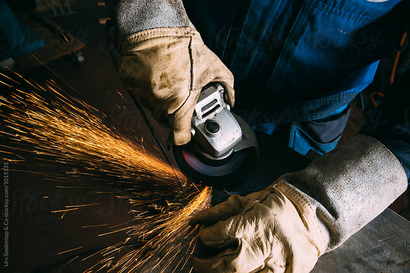 Metal worker with angle grinder  by Urs Siedentop & Co for Stocksy United