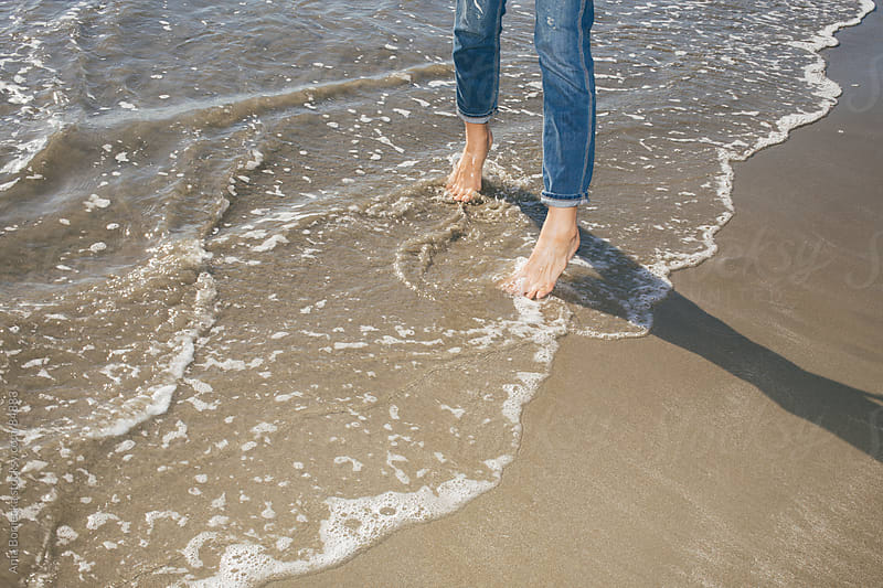 Feet playing in the sand and waves by Ania Boniecka for Stocksy United