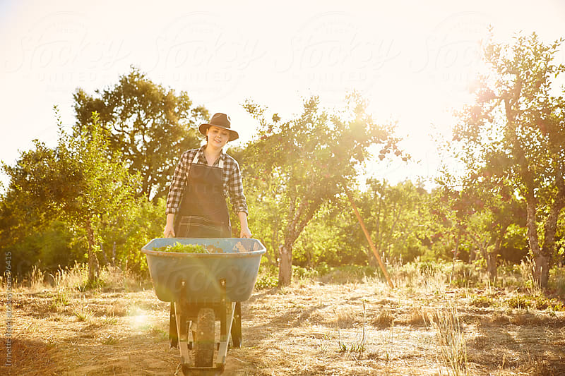 Woman farmer with wheel barrel and organic vegetables by Trinette Reed for Stocksy United