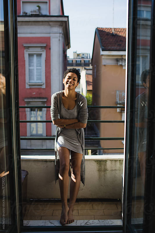 Smiling girl relaxes in the sun on the balcony by michela ravasio for Stocksy United