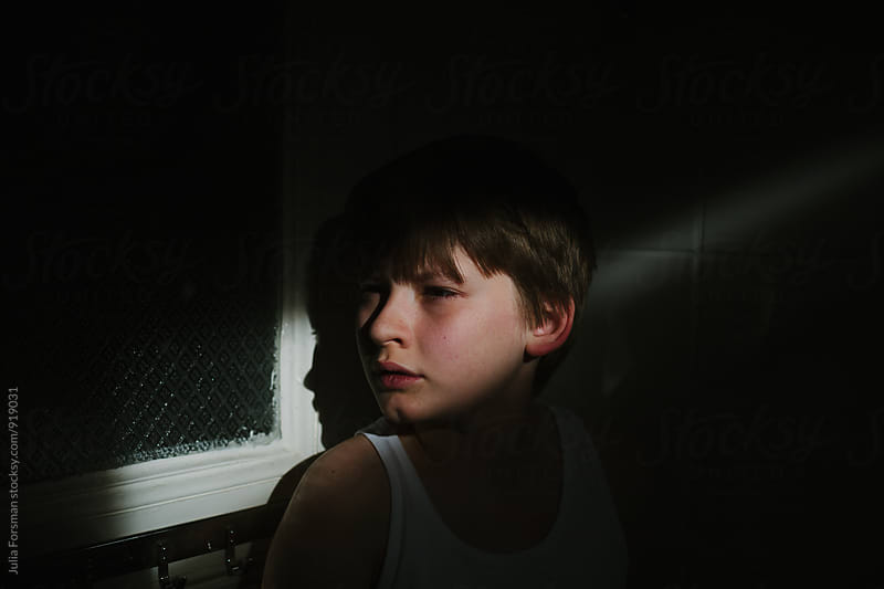 Pre teen boy standing in shadow and illuminated by shaft of sunlight. by Julia Forsman for Stocksy United