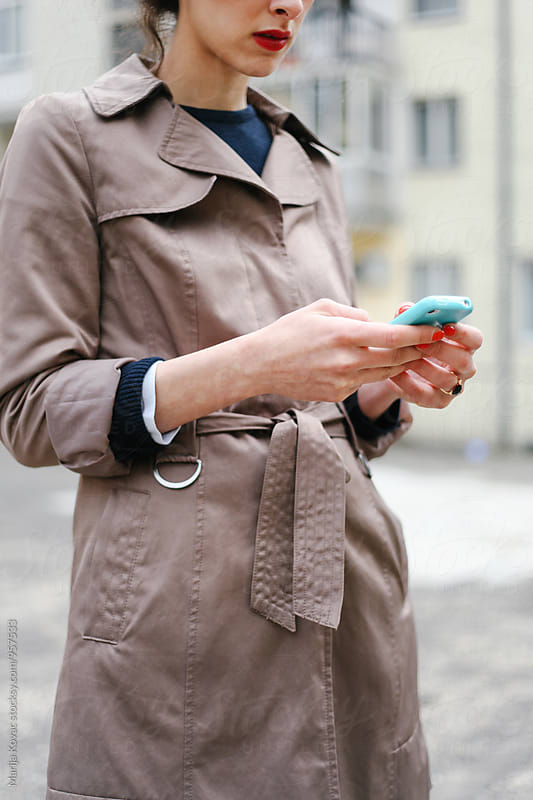 Female person holding a smart phone, vertical by Marija Kovac for Stocksy United