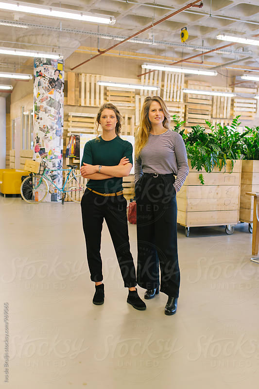 Portrait of two young women standing in their studio. by Ivo de Bruijn for Stocksy United