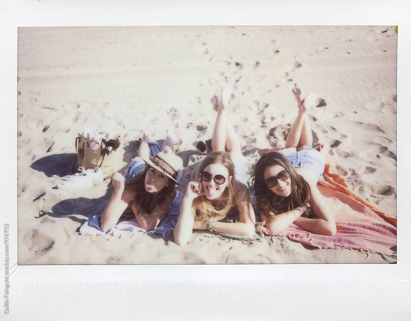 Three girlfriends on beach blanket sticking out tongues and smiling by Guille Faingold for Stocksy United