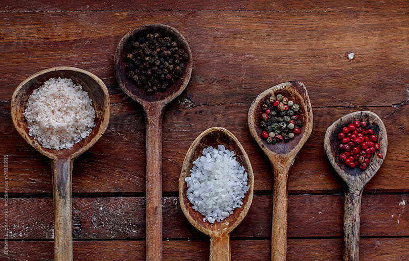 Different salt and peppercorn in Wooden Spoons by Babett Lupaneszku for Stocksy United
