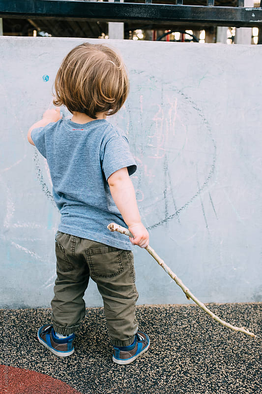 Young boy draws on a wally with chalk while holding a stick. by Lucas Saugen for Stocksy United
