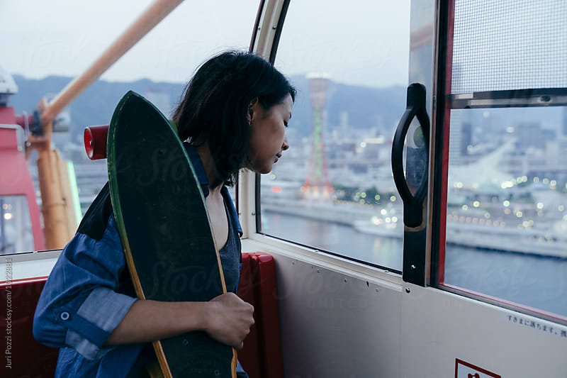 Asian girl looking at panorama from Kobe ferris wheel by Juri Pozzi for Stocksy United