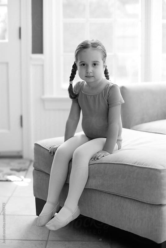 Cute young girl sitting on an ottoman in a ballet outfit by Jakob for Stocksy United