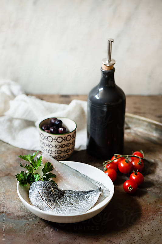 Seabream fillet with cherry tomatoes and black olives by Laura Adani for Stocksy United