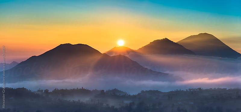 sunrise over volcanoes by Alexander Grabchilev for Stocksy United
