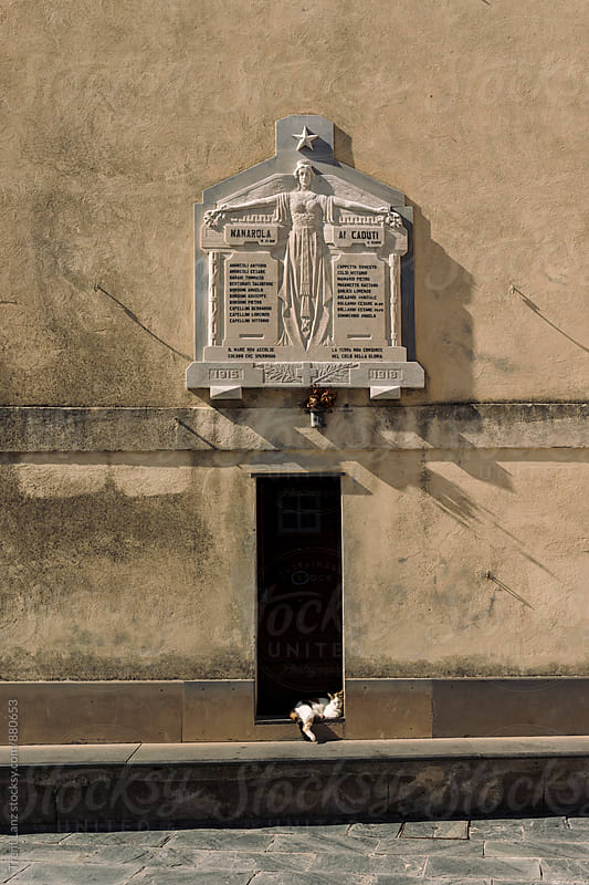 Cat sleeping in doorway under the sun in Italian Village by Trent Lanz for Stocksy United