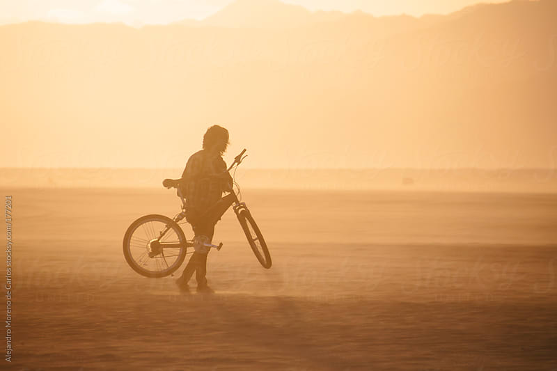 Man holding a bike on the beach at sunset by Alejandro Moreno de Carlos for Stocksy United