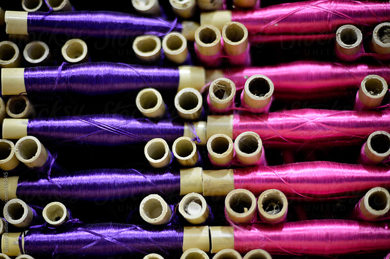 Spindles with different coloured yarn  by Bisual Studio for Stocksy United
