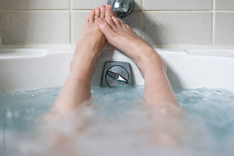Woman's Feet Relaxing in Bubbling Bathtub by Holly Clark for Stocksy United