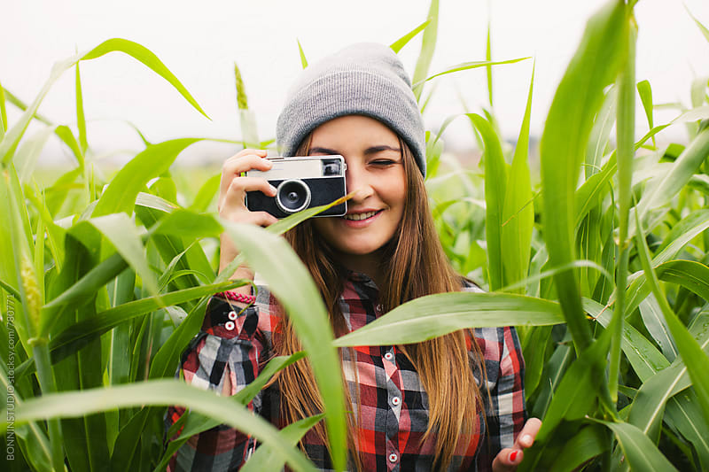 A 14 years old girl taking a photo in a corn field. by BONNINSTUDIO for Stocksy United
