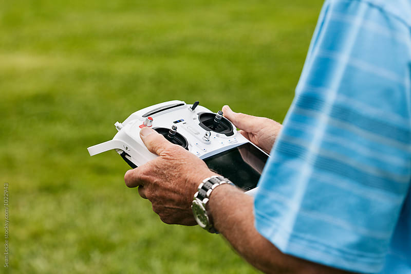 Man In Park Flyring Drone With Complex Remote Control by Sean Locke for Stocksy United