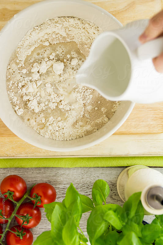 Make focaccia dough, pouring water into flour in mixing bowl by Kirsty Begg for Stocksy United