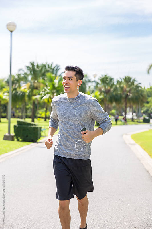 Handsome young man jogging alone in a park on a sunny day  by Jovo Jovanovic for Stocksy United