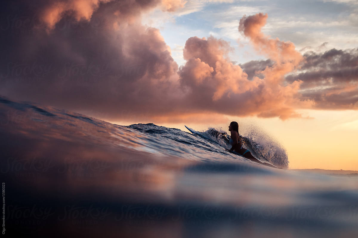 Stock Photo Silhouette Of Woman Surfing In The Ocean At Sunset Beautiful Clouds Vivid Warm Colors