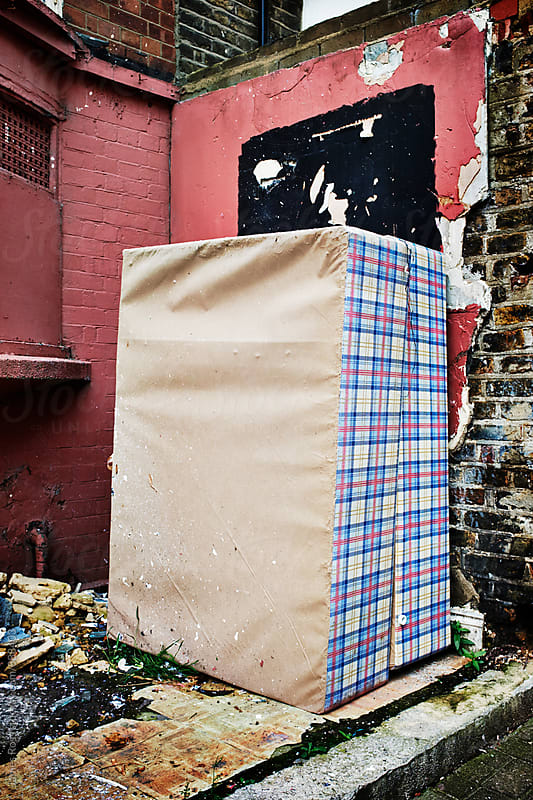 An abandoned bed by a wall by James Ross for Stocksy United