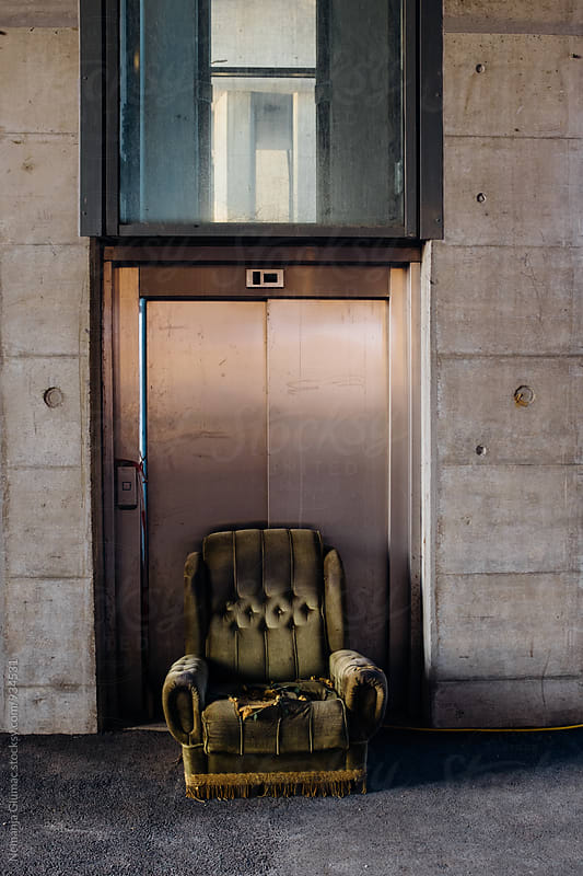Abandoned Green Sofa in Front of Public Elevator by Nemanja Glumac for Stocksy United