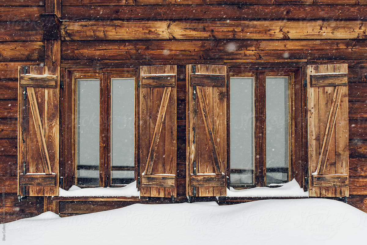 old wooden cabin window with snow outside stocksy united