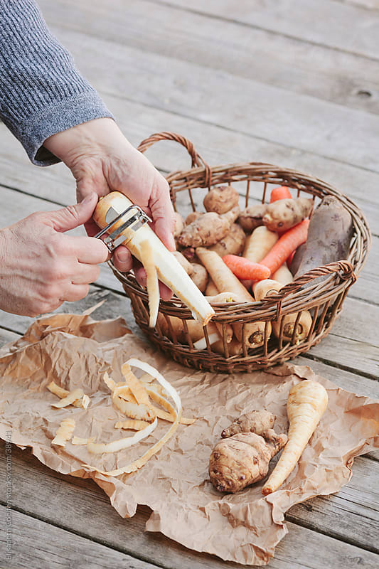 Man peeling parsnips  and other root vegetables outdoors by Elisabeth Coelfen for Stocksy United