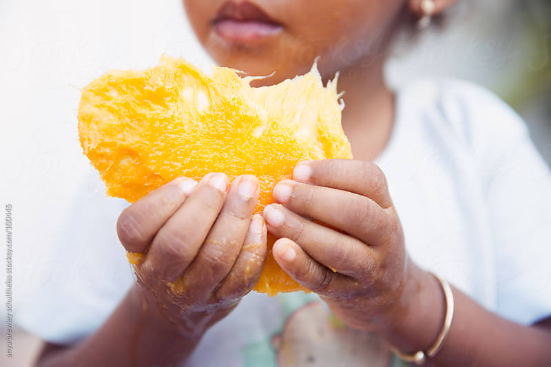 Close up of toddler eating a ripe mango by anya brewley schultheiss for Stocksy United