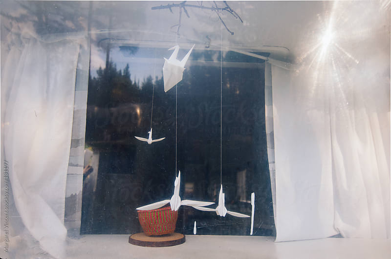 paper cranes in a vintage trailer window by Margaret Vincent for Stocksy United