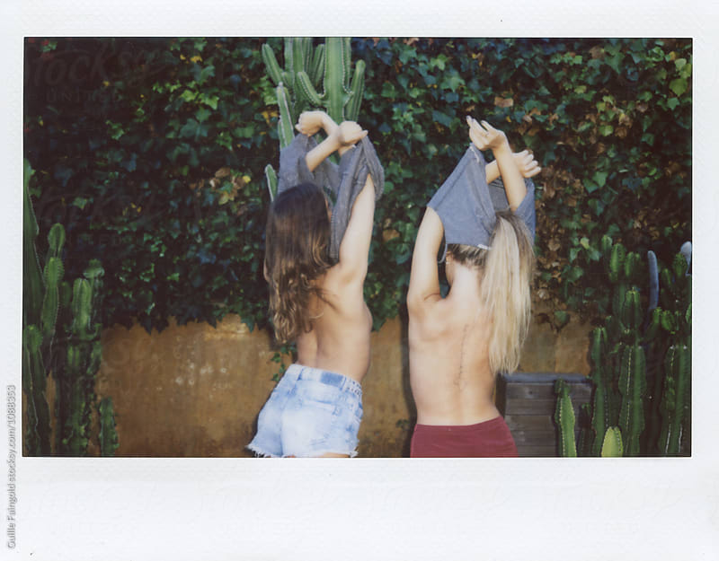 Back view of girlfriends taking off t-shirts in garden by Guille Faingold for Stocksy United