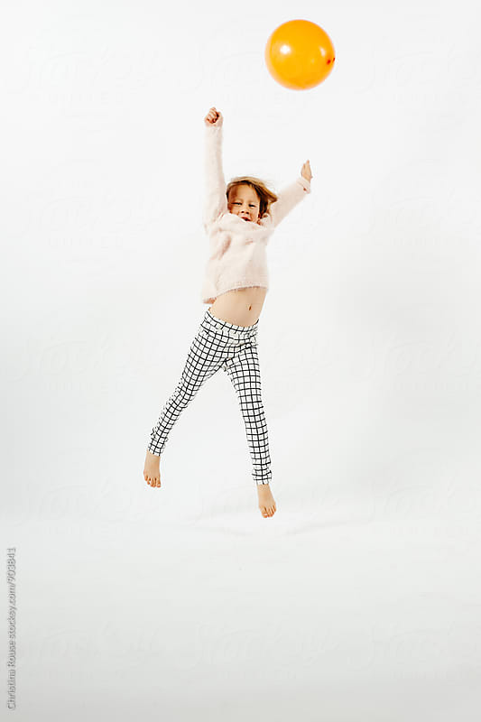Young girl jumps with an orange balloon against a white background by Christina Rouse for Stocksy United