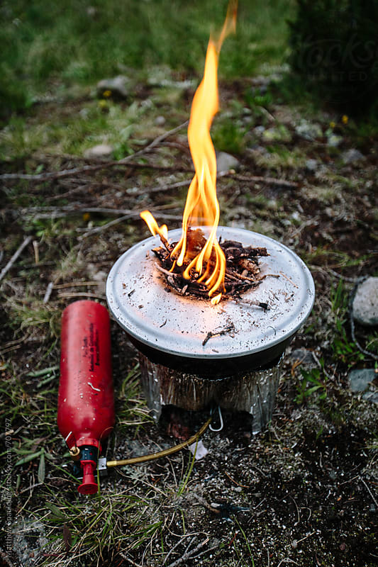 Camp stove with fire for backcountry baking outdoors by Matthew Spaulding for Stocksy United