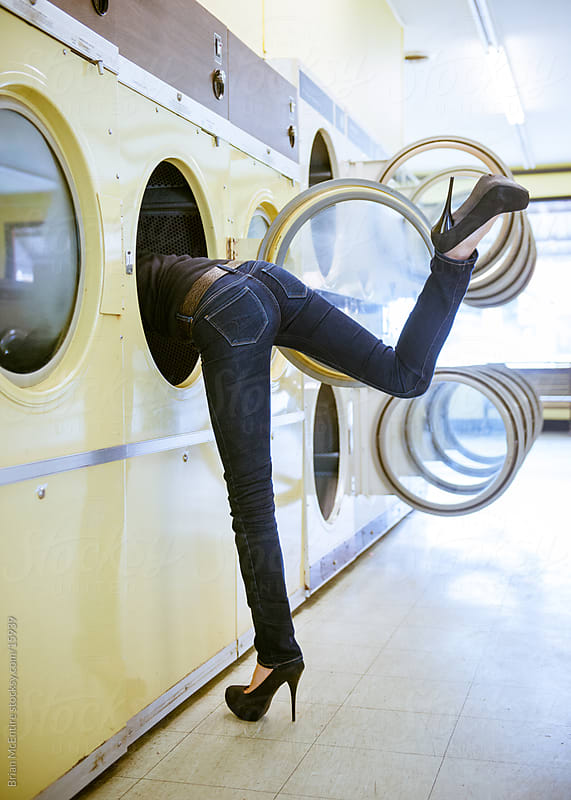 Laundromat: Woman Leaning In To Dryer by Brian McEntire for Stocksy United