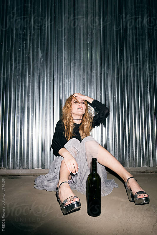 Portrait of blonde girl with eyes closed sitting on ground with bottle of wine by Danil Nevsky for Stocksy United