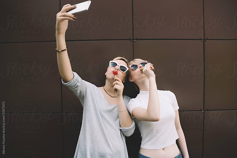 Teen girlfriends with candy taking a selfie by Alexey Kuzma for Stocksy United