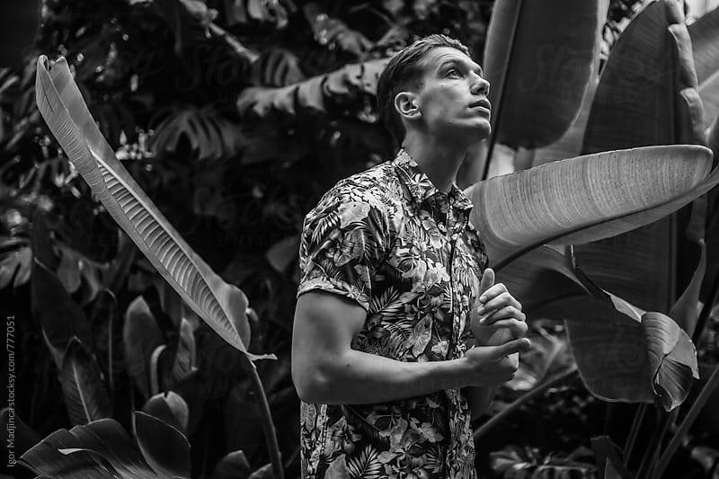 black and white portrait of fashionable man in floral shirt in nature by Igor Madjinca for Stocksy United