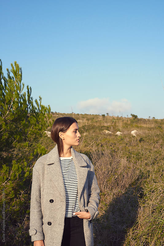 woman wearing grey coat posing on a plain by Guille Faingold for Stocksy United