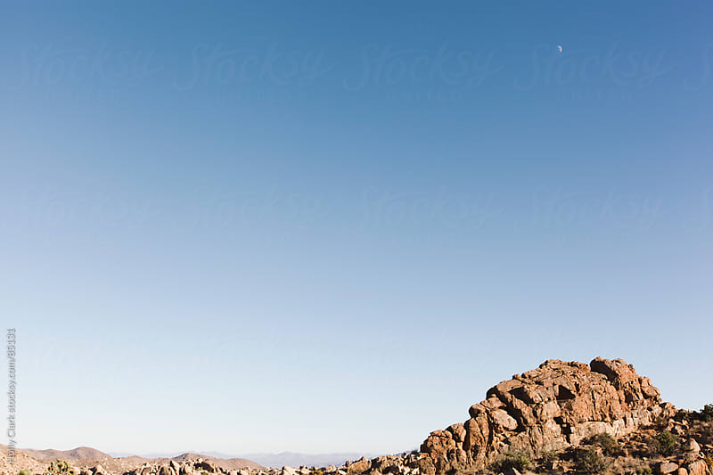 A minimal, boulder landscape under a waxing moon at twilight. by Holly Clark for Stocksy United