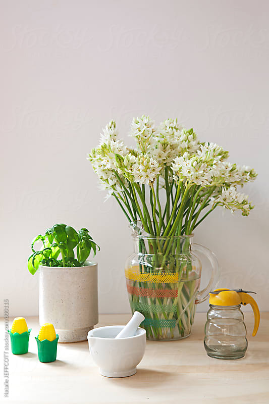 Tableau or kitchen vignette with flowers and basil and utensils by Natalie JEFFCOTT for Stocksy United