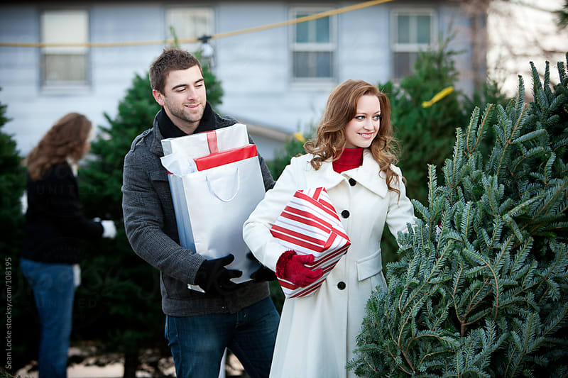 Tree Lot: Shopping Couple Looking For Christmas Tree by Sean Locke for Stocksy United