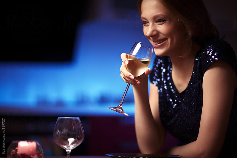 Young happy woman in restaurant with white wine by Ilya for Stocksy United
