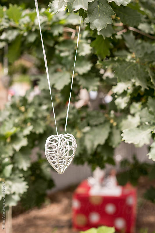 hanging heart shaped ornament in a tree by Gillian Vann for Stocksy United