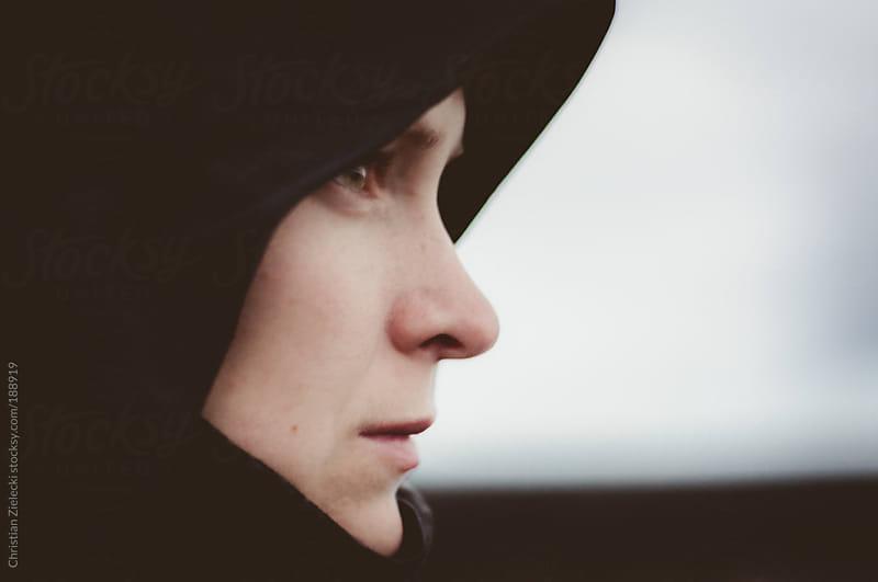 a side portrait of a woman wearing a hood by Chris Zielecki for Stocksy United