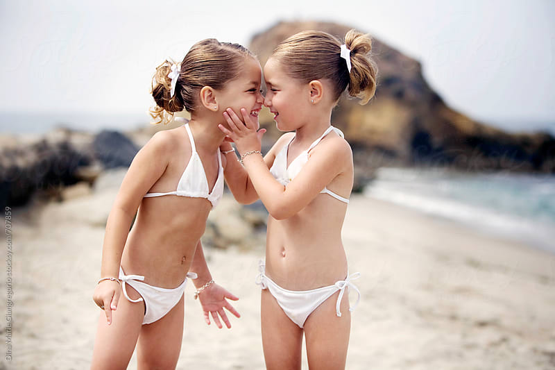 Twin Girls In Bathing Suits On Beach Face To Face by Dina Giangregorio for Stocksy United