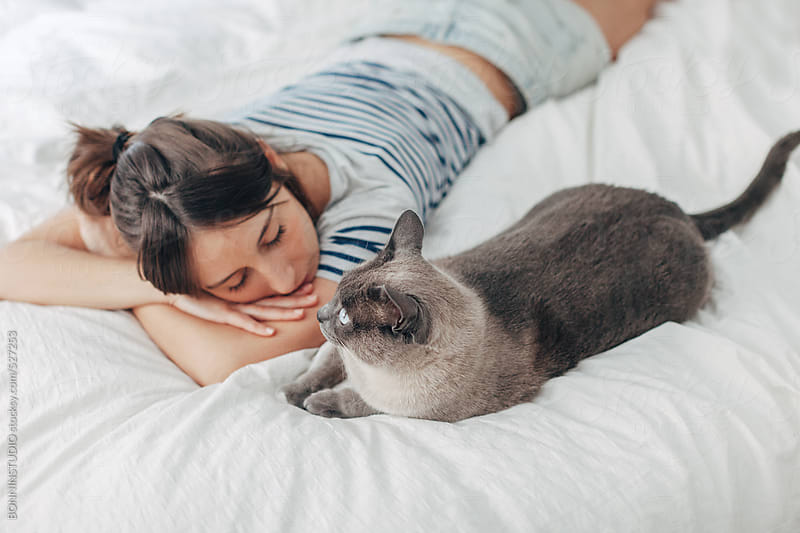 Young woman lying next to her beautiful cat in the bedroom. by BONNINSTUDIO for Stocksy United