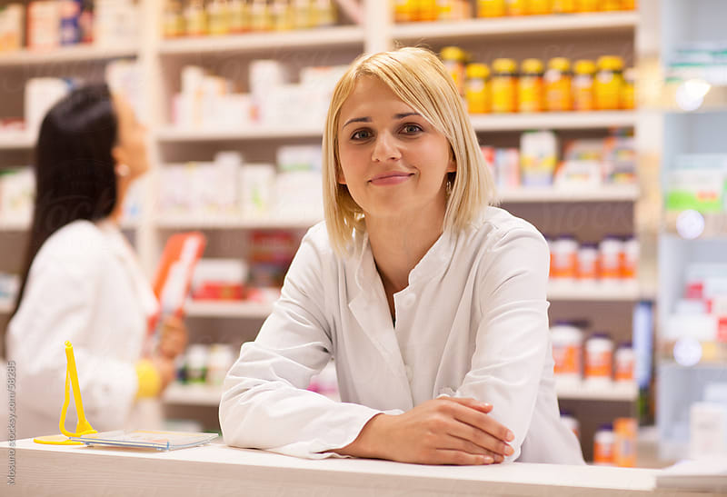 Pharmacist smiling over the counter. by Mosuno for Stocksy United